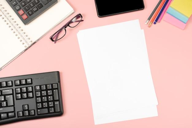 Widok z góry na różowe biurko z klawiaturą, smartfonem, okularami i materiałami eksploatacyjnymi.