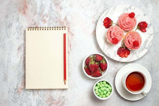Widok z góry na różowe ciasta truskawkowe z herbatą na białej powierzchni