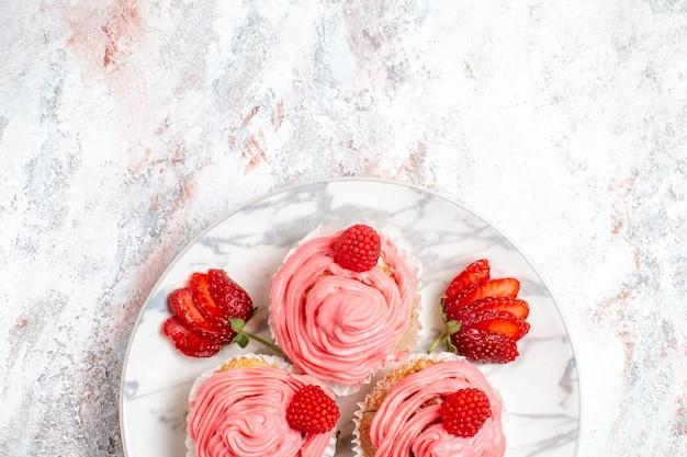 Widok z góry na różowe ciasta truskawkowe ze świeżymi jagodami na białej powierzchni