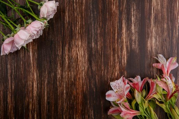 Widok z góry na różowe lilie z różowymi różami na drewnianej powierzchni