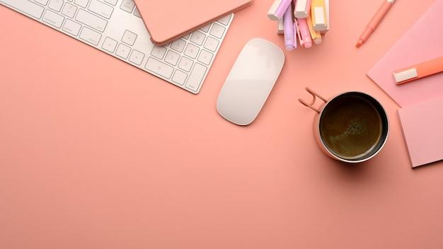 Widok z góry na różowy kreatywny stół do nauki z klawiaturą komputerową, myszą, elementami szkolnymi i przestrzenią do kopiowania