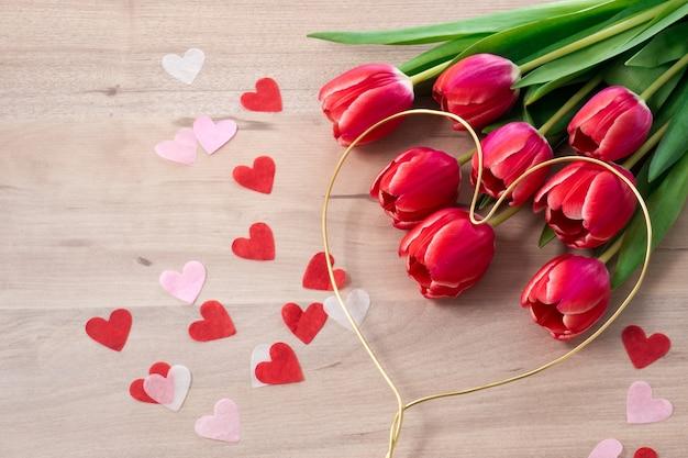 Widok z góry na różowy tulipan ze złotym sercem i konfetti na walentynki