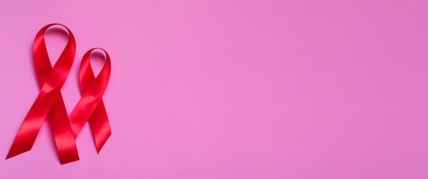 Widok z góry na różowym tle z czerwoną wstążką koncepcji 1 grudnia zbliżenie międzynarodowy dzień aids. transparent