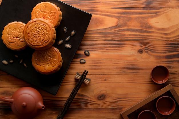 """Widok z góry na rustykalny stół z zestawem do herbaty, ciastka księżycowe na pustym talerzu ceramicznym i miejsce na kopię. chińskie znaki na księżycowym cieście oznaczają w języku angielskim """"pięć ziaren i pieczeń wieprzową"""""""