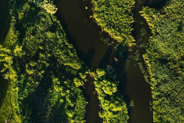 Widok z góry na rzekę świsłocz w parku i kajakarz o zachodzie słońca w mińsku. piękna przyroda białorusi.
