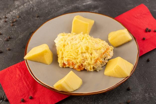 Widok z góry na sałatkę warzywną z majonezem, kurczakiem w środku i świeżym serem na talerzu na szarym biurku