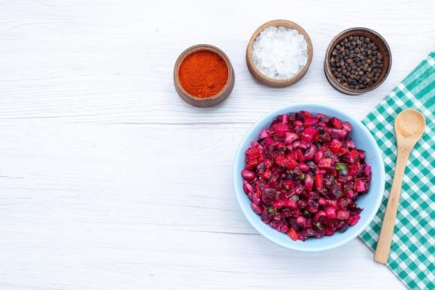 Widok z góry na sałatkę z buraków pokrojoną w zieleninę wewnątrz niebieskiego talerza z przyprawami na lekkim biurku, witaminowy posiłek warzywny, zdrowa sałatka
