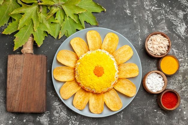 Widok z góry na sałatkę z ziołami i deskę do krojenia na stronie z liśćmi na wierzchu na ciemnoszarym stole