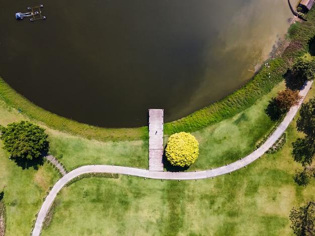 Widok z góry na scenerię drewnianego molo nad jeziorem z zielonym trawnikiem i ścieżką