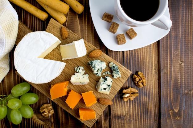 Widok z góry na sery, paluszki do kawy i chleba na brązowym drewnianym