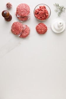 Widok z góry na składniki do robienia hamburgera. w marmurowym stole szklana miska z mięsem,