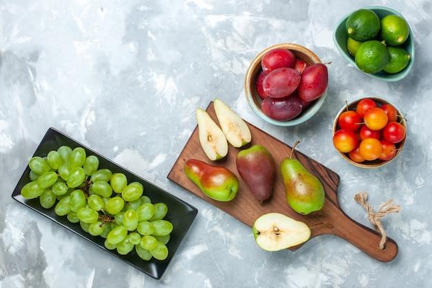 Widok z góry na śliwki i cytryny z gruszkami i winogronami na jasnobiałej powierzchni
