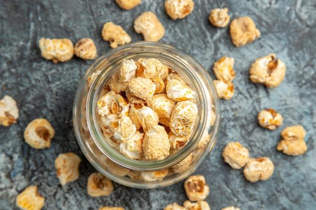 Widok z góry na słodki popcorn w szklanej puszce na jasnej powierzchni