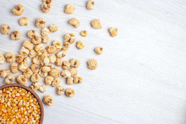 Widok z góry na słodki popcorn z surowymi ziarnami na jasnej powierzchni