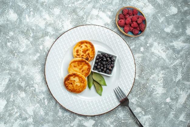 Widok z góry na słodkie babeczki z jagodami wewnątrz płyty na jasnej powierzchni