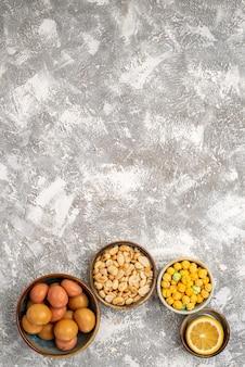 Widok z góry na słodkie cukierki z orzechami i cytryną na jasnobiałej powierzchni