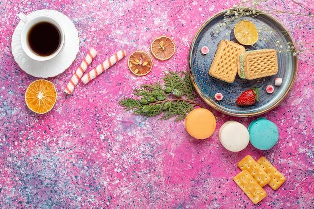 Widok z góry na słodkie gofry z filiżanką herbaty na jasnoróżowej powierzchni