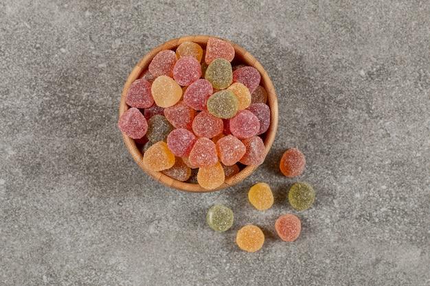 Widok z góry na słodkie kolorowe marmolady w drewnianej misce.