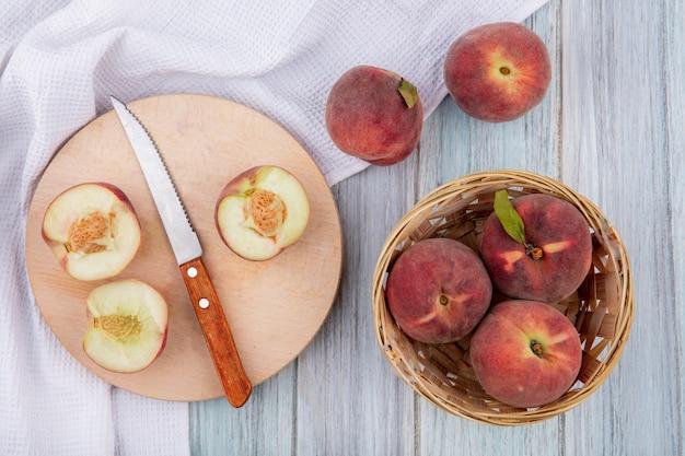 Widok z góry na słodkie pyszne brzoskwinie na drewnianej desce kuchennej z nożem z koszem brzoskwiń na szarej drewnianej powierzchni