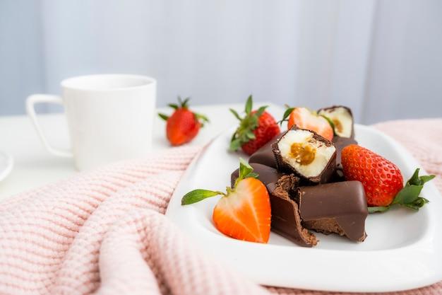 Widok z góry na słodkie śniadanie. śniadanie ze słodkim twarogiem w czekoladzie, truskawkami i filiżanką kawy.
