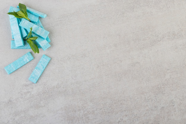 Widok z góry na słodko-gorzkie dziąsła z listkami mięty na szarej powierzchni