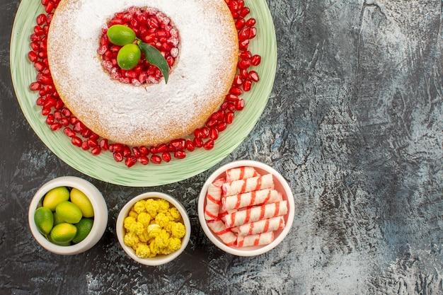 Widok z góry na słodycze apetyczny tort z pestkami granatu miski cukierków i limonek