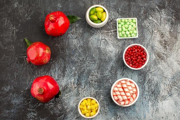 Widok z góry na słodycze miski kolorowych cukierków granat owoce cytrusowe