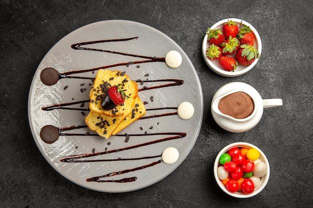 Widok z góry na słodycze talerz apetycznego ciasta z truskawkami i czekoladą obok misek z cukierkami truskawkowymi i sosem czekoladowym