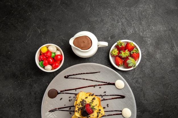 Widok z góry na słodycze talerz smakowitych kawałków ciasta z sosem czekoladowym i truskawkami obok misek cukierków, truskawek i sosu czekoladowego