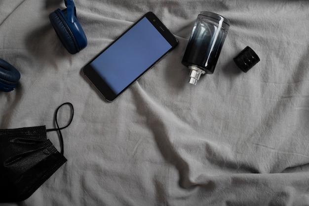 Widok z góry na słuchawki do telefonu komórkowego męskie perfumy i jednorazową czarną maskę
