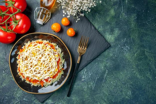 Widok z góry na smaczną sałatkę z mimozy wewnątrz talerza na ciemnoniebieskiej powierzchni