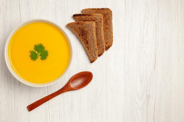 Widok z góry na smaczną zupę dyniową z teksturą z ciemnymi bochenkami chleba na białym