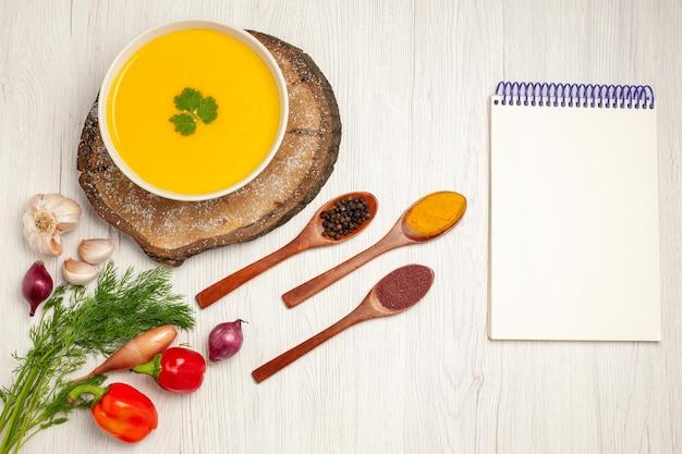 Widok z góry na smaczną zupę dyniową z zieleniną na białym tle