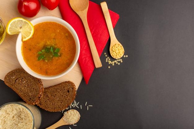 Widok z góry na smaczną zupę jarzynową wewnątrz talerza z olejem z plasterków cytryny i chlebem na ciemnej powierzchni