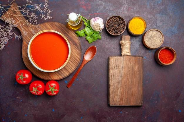 Widok z góry na smaczną zupę pomidorową z przyprawami i świeżymi pomidorami w ciemności