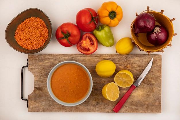 Widok z góry na smaczną zupę z soczewicy na misce na drewnianej desce kuchennej z cytrynami z nożem z czerwoną cebulą na wiadrze z pomidorami i papryką odizolowaną na białej ścianie