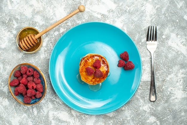 Widok z góry na smaczne babeczki z jagodami i miodem na jasnej powierzchni