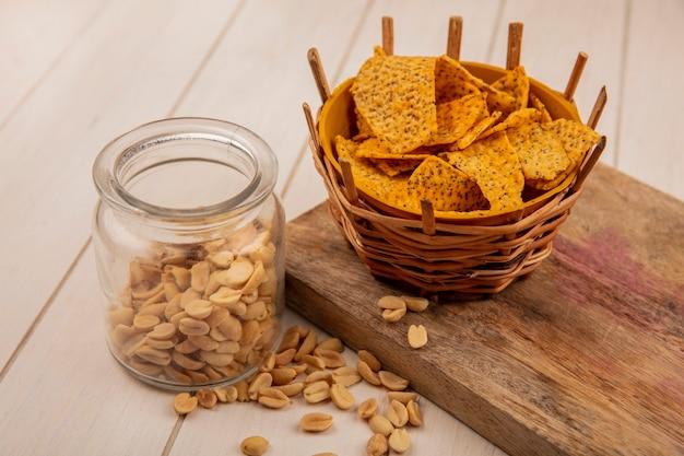 Widok z góry na smaczne chrupiące i pikantne frytki na wiadrze na drewnianej desce kuchennej z orzeszkami piniowymi na szklanym słoju na beżowym drewnianym stole
