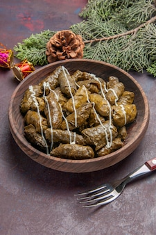 Widok z góry na smaczne danie mięsne dolma z liści wewnątrz brązowego talerza na ciemnej przestrzeni