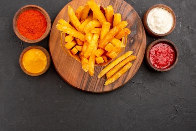 Widok z góry na smaczne frytki z sosami na czarno?