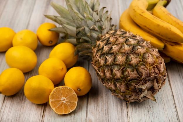 Widok z góry na smaczne owoce, takie jak ananas, banany i cytryny, odizolowane na szarej drewnianej powierzchni