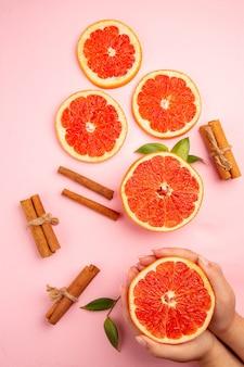 Widok z góry na smaczne plasterki owoców grejpfruta z cynamonem na różowej powierzchni