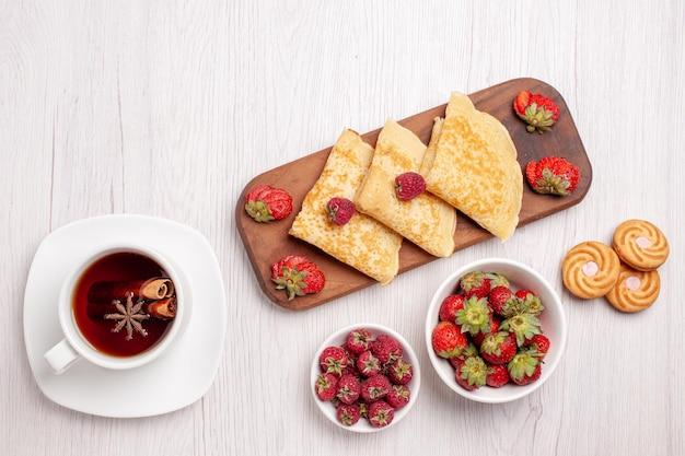 Widok z góry na smaczne słodkie naleśniki z jagodami i filiżanką herbaty na białym