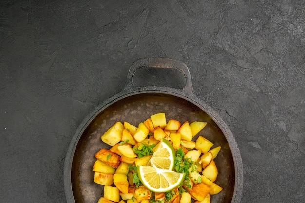 Widok z góry na smaczne smażone ziemniaki na patelni z plasterkami cytryny na ciemnej powierzchni