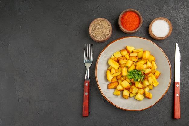 Widok z góry na smaczne smażone ziemniaki wewnątrz talerza z przyprawami na ciemnej powierzchni