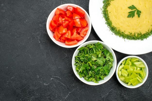 Widok z góry na smaczne tłuczone ziemniaki z zieleniną i świeżymi pokrojonymi pomidorami na szarej przestrzeni