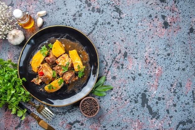Widok z góry na smaczny obiad z mięsnymi ziemniakami podany z zielonym w czarnym talerzu i zestawem sztućców do butelek z czosnkiem i pieprzem