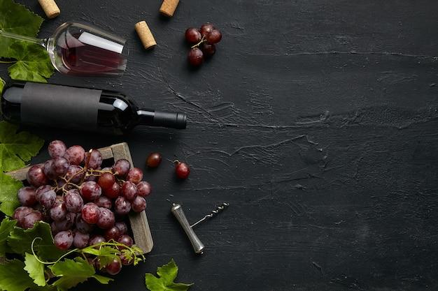 Widok z góry na smaczny talerz owoców z butelką wina i szklanką na czarnym kamieniu na płycie kuchennej na czarnym tle kamienia, widok z góry, miejsce. jedzenie i picie dla smakoszy.