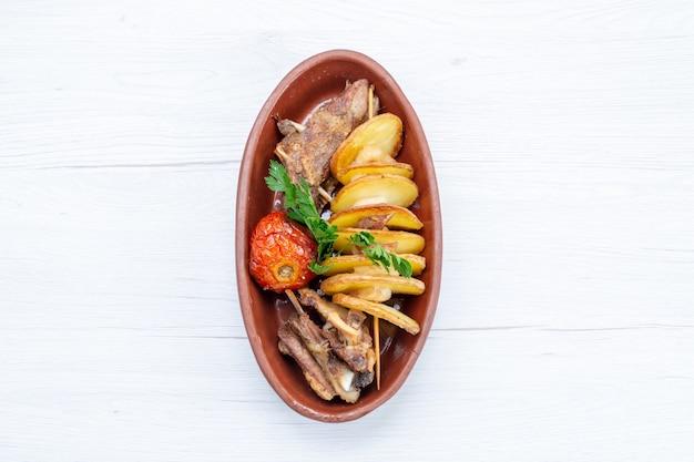 Widok z góry na smażone mięso z zieleniną i pieczonymi śliwkami wewnątrz brązowego talerza na lekkim, obiadowym daniu mięsnym