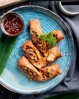 Widok z góry na smażone sajgonki z kurczakiem i warzywami podawane z sosem sojowym na talerzu na czarno
